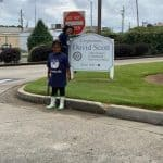Ana Garica-Ashley and her granddaughter stand next to the sign for Rep. David Scott's office.
