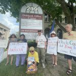 Members of Casa Esther hold signs in front of Sen. Ron Johnson's office.